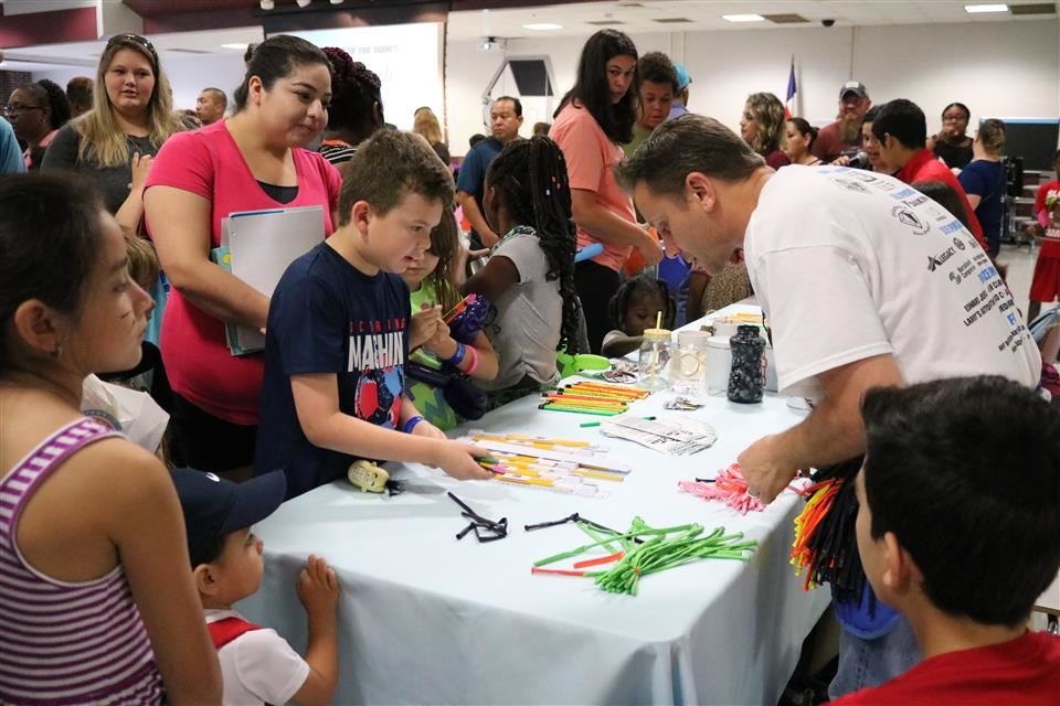 Photo of families receiving their backpacks at the Waller ISD Back to School Fair